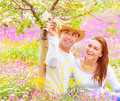 Young family having fun outdoors cute girl with attractive guy looking on blooming flowers romantic relationship love and Stock Photo