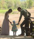 Young family, mother, father, daughter, walk in the city park Royalty Free Stock Photo