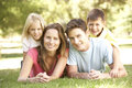 Young Family Relaxing Together In Park Royalty Free Stock Photo