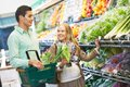 Young family at store man and pregnant women choosing fresh fruits or greens during shopping bakery supermarket Royalty Free Stock Images
