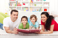Young family with two kids reading a story book Royalty Free Stock Photo