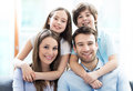 Young family with two kids smiling relaxing at home Stock Image