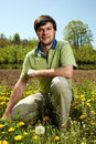 Young farmer outdoor knelt near his land in a sunny day Stock Photos
