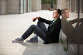 Young fashion business man with mobile phone sitting at the wall Royalty Free Stock Photo