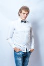 Young fashion male model wearing bow tie on gray and jeans background Stock Images
