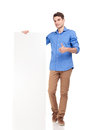 Young fashion man holding a empty board full body picture of while showing the thumbs up gesture Stock Photos