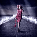 Young fashion woman is on pier during storm in red dress and hatis the sea a and rain holding handbag Royalty Free Stock Photography
