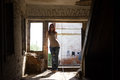 Young fashionable attractive sexy girl in glasses and jeans stands inside a destroyed building at sunny summer midday Royalty Free Stock Photo