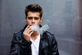 Young fashionable man smoking a cigarette with copy space looking to the camera portrait of confident exhaling Royalty Free Stock Photos