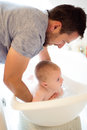 Young father bathing his son in white small plastic bath Royalty Free Stock Photo