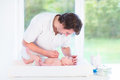 Young father changing a diaper at his little baby son looking Stock Photography