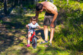 Young father helping daughter to ride bicycle a Stock Photography