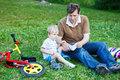 Young father helping his son with shoes on green grass after having a ride bicycle Royalty Free Stock Images