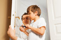 Young father helping his son to fix door-handle Royalty Free Stock Photo