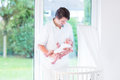 Young father holding his newborn baby next to crib Royalty Free Stock Photo