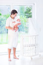 Young father holding his newborn baby next to crib smiling standing a white rond Royalty Free Stock Images