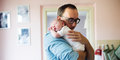 Young father holding newborn baby son in his arms Royalty Free Stock Photo