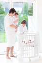 Young father with kids next tt white crib Royalty Free Stock Photo