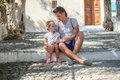 Young father with little daughters have a rest on street in old greek town this image has attached release Royalty Free Stock Photos