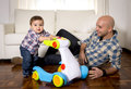 Young father and little son walking with baby walker taking his first brave steps happy one year old at home in living room Royalty Free Stock Image