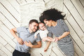 Young father, mother and cute baby lying on floor Royalty Free Stock Photo