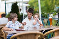 Young father in outside cafe with his children relaxing an Stock Photo