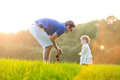 Young father playing with his baby daughter in a f field on sunny autumn evening Royalty Free Stock Photo