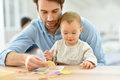Young father playing with his baby girl man at home Stock Image