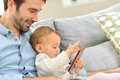 Young father playing with his baby on smarpthone daddy and girl smartphone Stock Photos