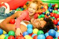Young father playing with his daughter inside ball pit swimming pool - Happy people having fun in children playground indoor -