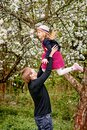 A young father plays with his daughter in a flowering garden. Throws up. Against the background of green grass and flowering trees