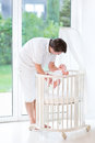 Young father putting his newborn baby into crib happy smiling a white round Stock Photography