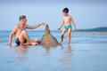 Young father and son building sand castle at beach his little Stock Photos