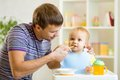 Young father teaches his baby son to eat with spoon Royalty Free Stock Photo