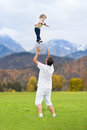 Young father throwing his baby high in the sky Royalty Free Stock Photo