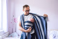 Young father wrapping his newborn baby son into sling Royalty Free Stock Photo