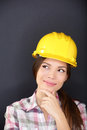 Young female architect engineer or surveyor construction worker wearing hardhat thinking as she standing with hand to chin looking Royalty Free Stock Photography