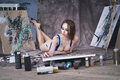 Young female artist painting abstract picture in studio, beautiful sexy woman portrait Royalty Free Stock Photo