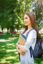 Young female asian IT student, with books and backpack. Staying in the park and smiling Royalty Free Stock Photo