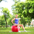 Young female athlete sitting on a pilates ball in park and looking at camera shot with tilt and shift lens Royalty Free Stock Photo