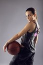 Young female basketball player posing on grey background portrait of looking over shoulder at camera against Royalty Free Stock Photography