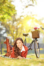 Young female with bicycle in a park on a sunny day lying grass Royalty Free Stock Photos