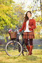 Young female with bicycle posing in park a and looking at camera Stock Image