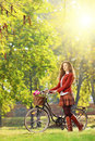 Young female with bicycle relaxing in a park on sunny day Royalty Free Stock Photos