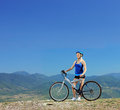 A young female biker posing with a mountain bike outdoors Royalty Free Stock Photography