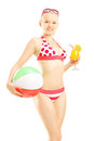 Young female in bikini holding a beach ball and cocktail isolated on white background Stock Photo