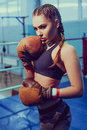 Young female boxer ready to fight in old leather boxing gloves. fitness happy blonde girl in sport wear with perfect body Royalty Free Stock Photo