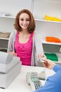 Young female cashier with cash register happy at counter Stock Photos