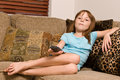 Young female child relaxing watching television sitting corner couch holding t v remote control Royalty Free Stock Photo