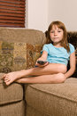 Young female child relaxing watching television sitting corner couch holding t v remote control Stock Photos